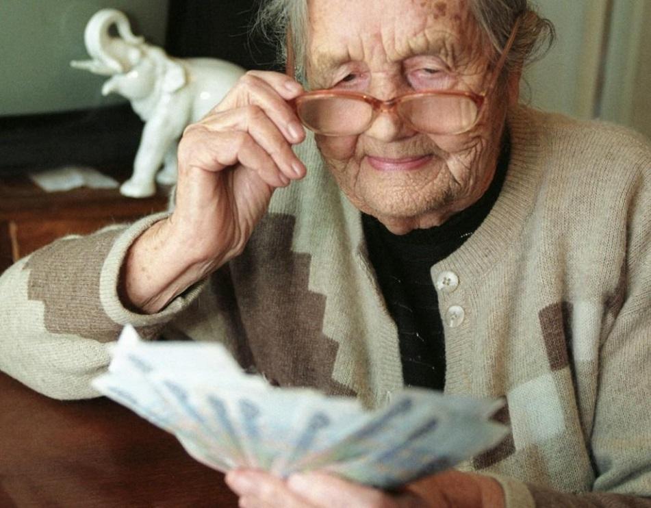 Пенсионерка держит в руках купюры